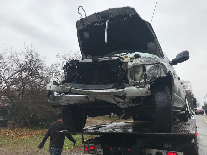 A pickup involved in a head-on collision on Airport Road on Sunday is loaded onto a tow truck.