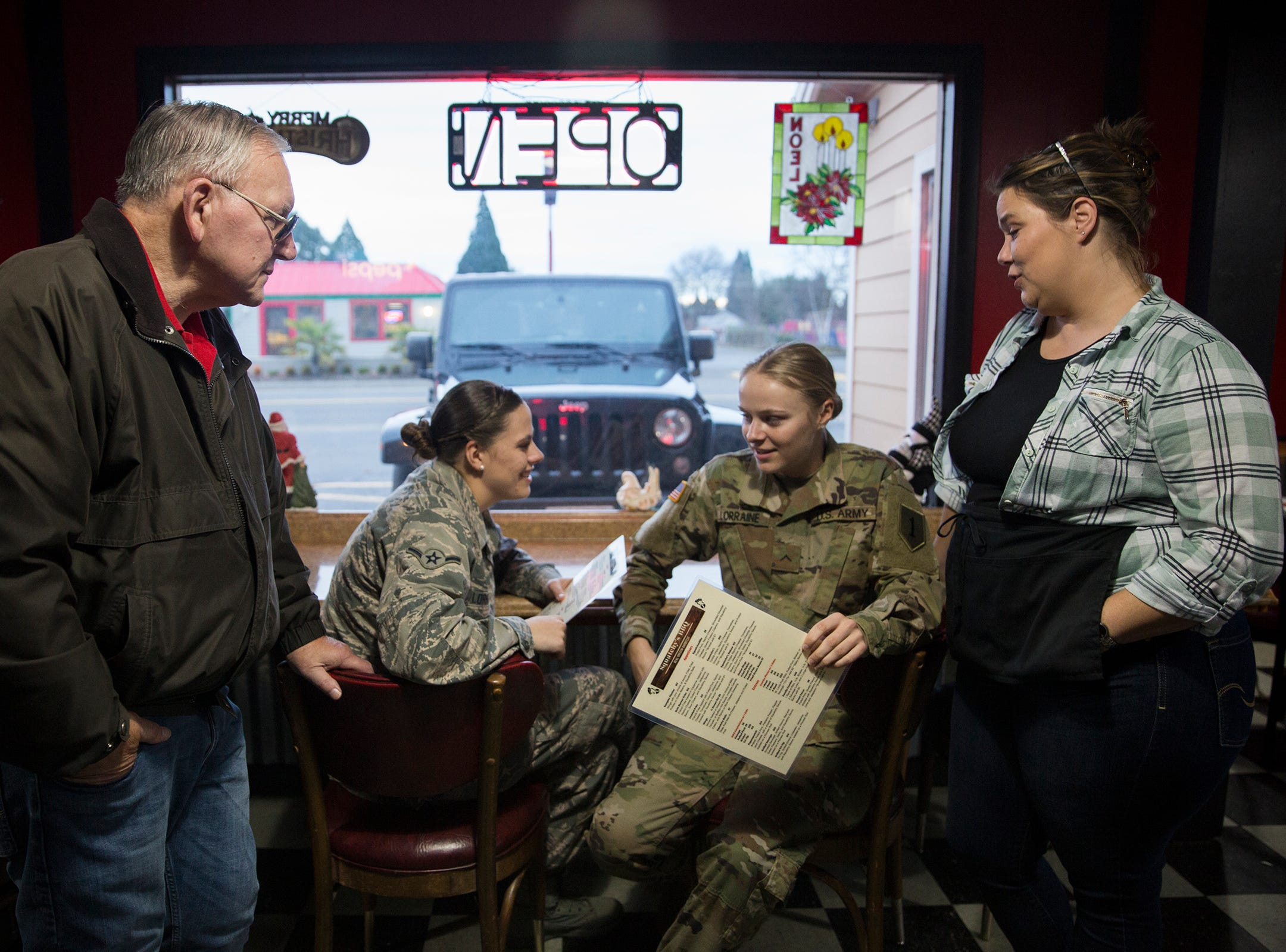 Military sisters Kelsey Lorraine and Courtney Lorraine talk to their mom Julie and grandfather Jerry after Courtney surprised them at their family restaurant Squatchy's BBQ in Stayton on Saturday, Dec. 22, 2018.