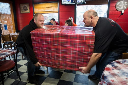 Jason Lorraine (right) carries in a present for his wife with help from his nephew Christopher Kinn (left) at Squatchy's BBQ in Stayton on Thursday, Dec. 20, 2018. Inside the box is his military daughter Courtney Lorraine.
