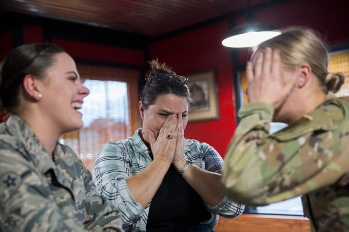 Julie Lorraine (center) wipes tears away after her youngest daughter Courtney (right) surprised her and her other other daughter Kelsey (left) at their family restaurant Squatchy's BBQ in Stayton on Saturday, Dec. 22, 2018.
