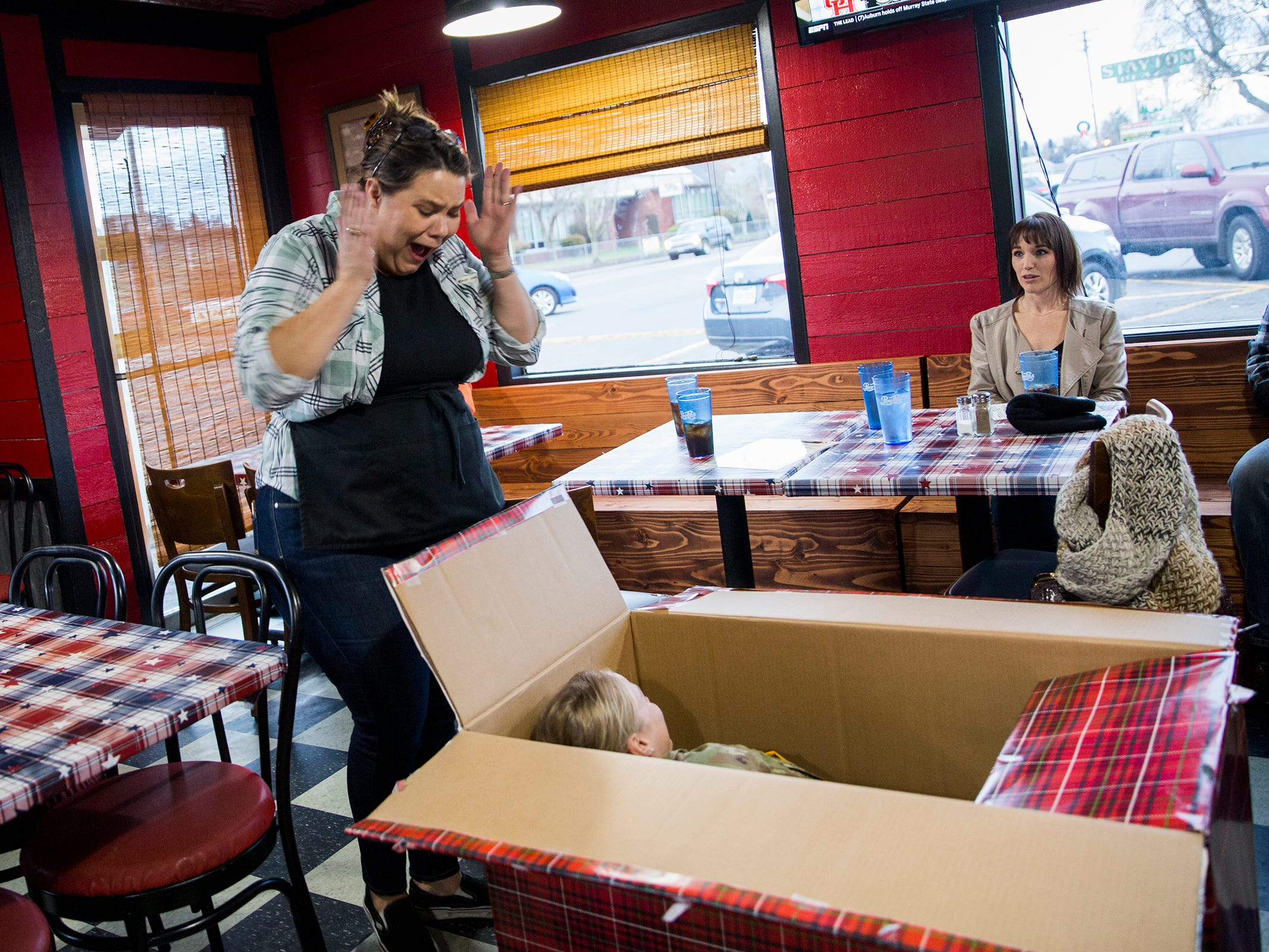 Julie Lorraine opens a present from her husband at her restaurant Squatchy's BBQ in Stayton on Saturday, Dec. 22, 2018. The present is her military daughter Courtney who she thought was still at basic training.