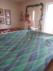 La Verne Redman attaches a quilt layer to her frame Monday, Dec. 18, 2018. The frame at her home in Miles, Texas, is made from dining room chairs and four poles.
