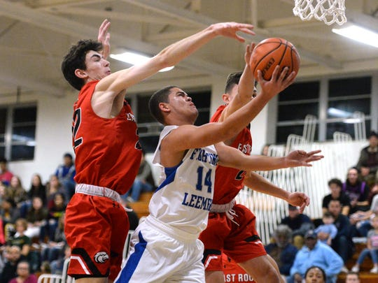 Lee High's Nicholas Jones puts up a shot between two East Rockingham defenders Saturday night in the Paul Hatcher Gym.