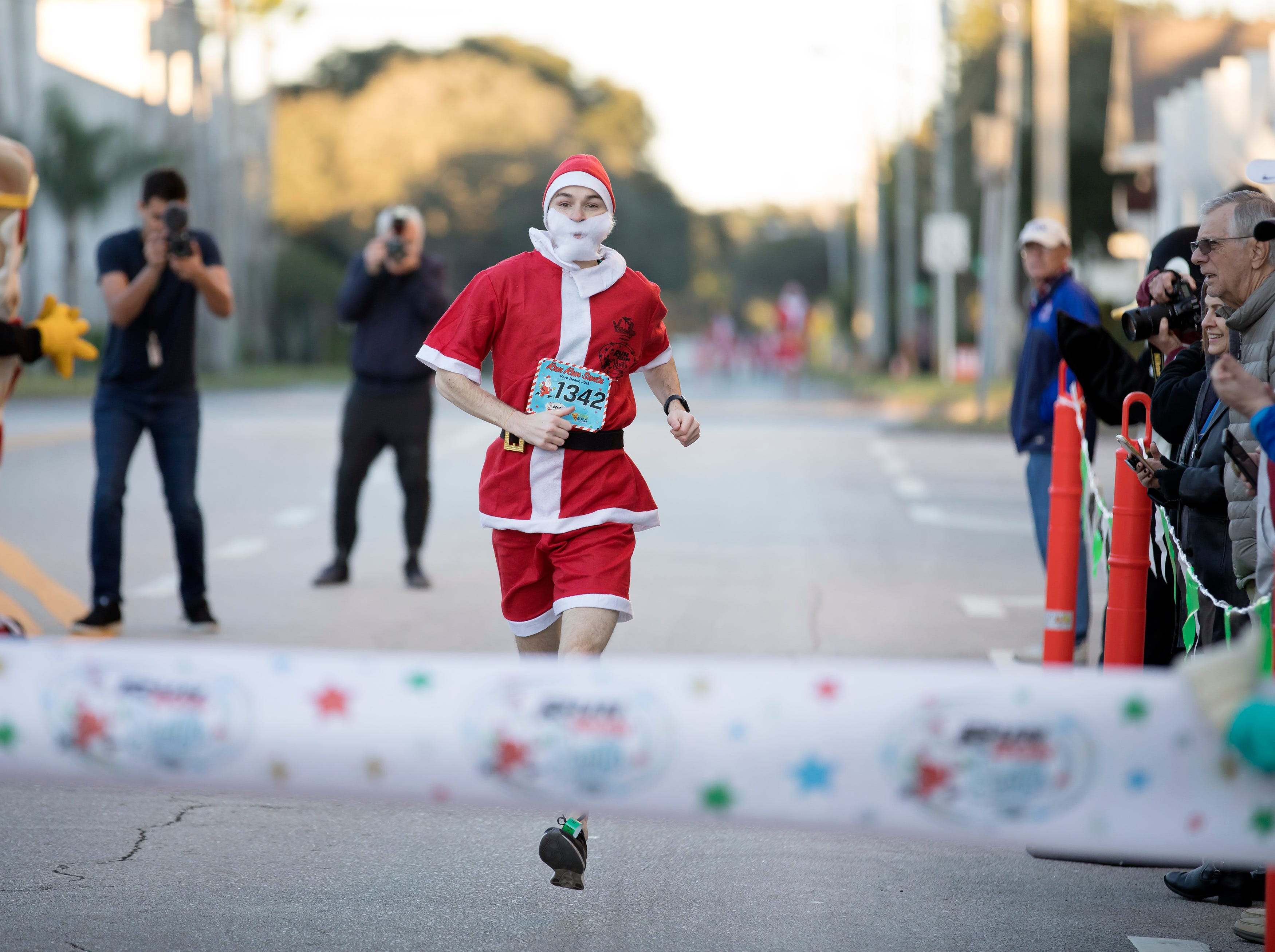 Michael Ellenburger, of Chicago, crosses the finish line after winning the Run Run Santa one-mile race Sunday, Dec. 23, 2018, through downtown Vero Beach. Ellenburger finished with a time of 5:01.81.