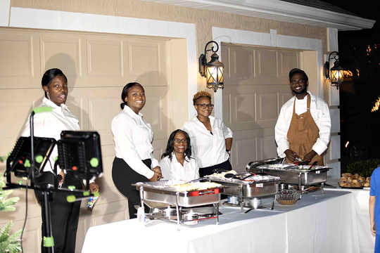 """Tim and Brittany Holdy provided theirneighbors with a special holiday dinner prepared by private Chef Howard Farro, pictured here at right with servers at the Dec. 8 """"Santa in The Pines"""" party."""