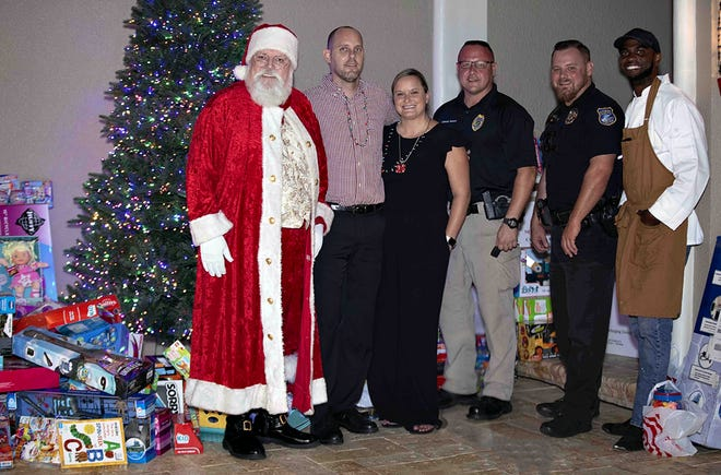 """Santa Claus, left, with Tim and Brittany Holdy, Stuart Police Department Sgt. Brian Bossio and Officer Corey Lee and Chef Howard Farro at the Dec. 8 """"Santa in The Pines"""" party where neigbors donated 273 toys for the United Way of Martin County White Doves Holiday Project and Marine Toys for Tots Foundation."""