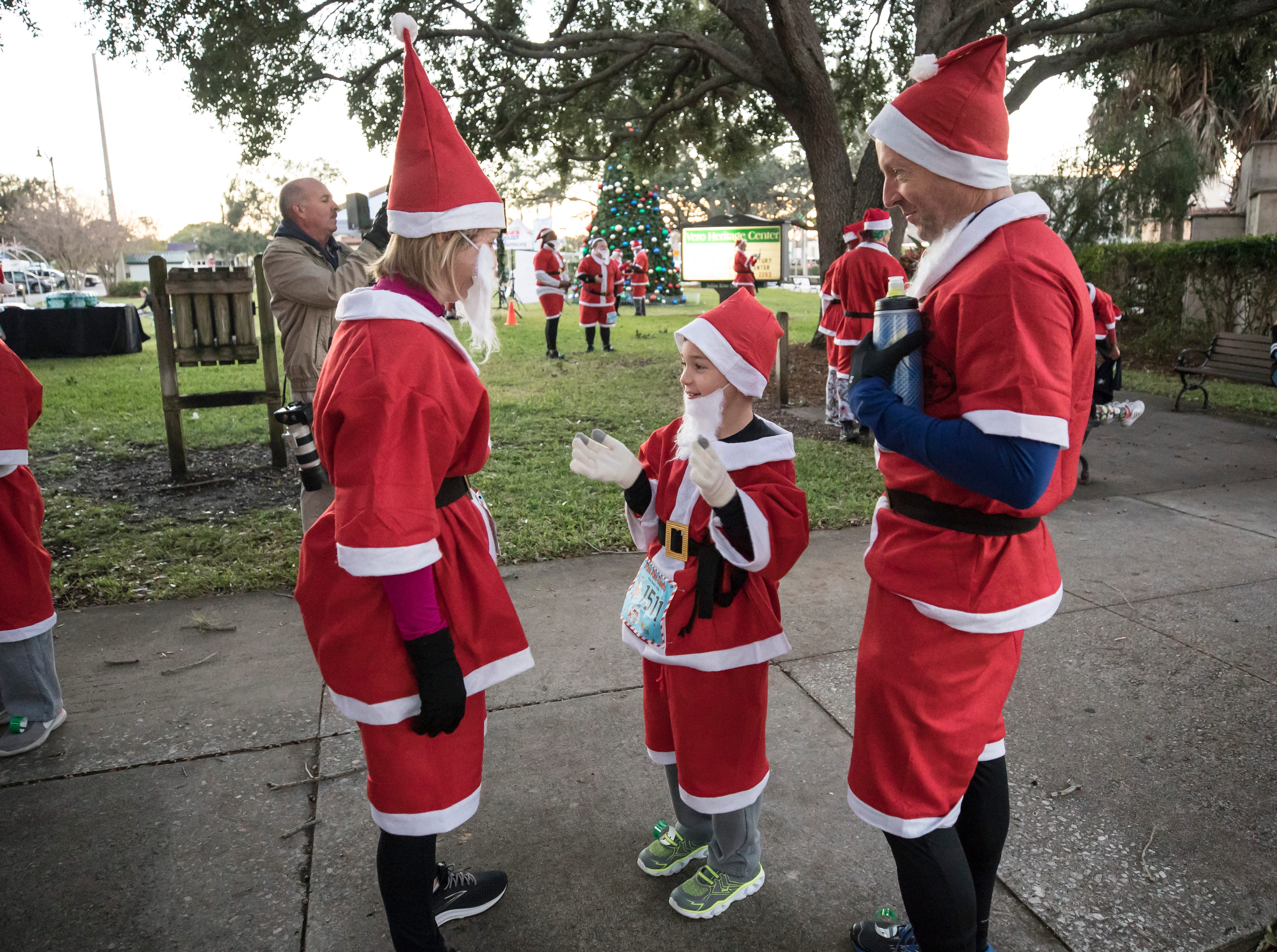 """Elysia Brennan (left) gets ready for the Run Run Santa one-mile race with her 7-year-old son, Cole, and husband, Ryan, on Sunday, Dec. 23, 2018, in Vero Beach. ""They didn't know (they were going to race),"" laughed Elysia. ""I signed them up. I was like, 'I have this big surprise'. It's going to be a new tradition. We do this and go get breakfast every year. It seemed like a fun way to get into the holiday spirit."""