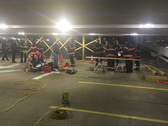 Yonkers firefighters temporarily shore up the parking structure in Cross County Mall after a driver slammed into a wall.