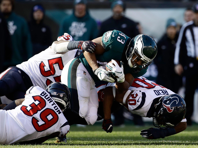 Philadelphia Eagles' Darren Sproles (43) is tackled by Houston Texans' Justin Reid (20), Deante Burton (39) and Benardrick McKinney (55) during the first half of an NFL football game, Sunday, Dec. 23, 2018, in Philadelphia. (AP Photo/Matt Rourke)