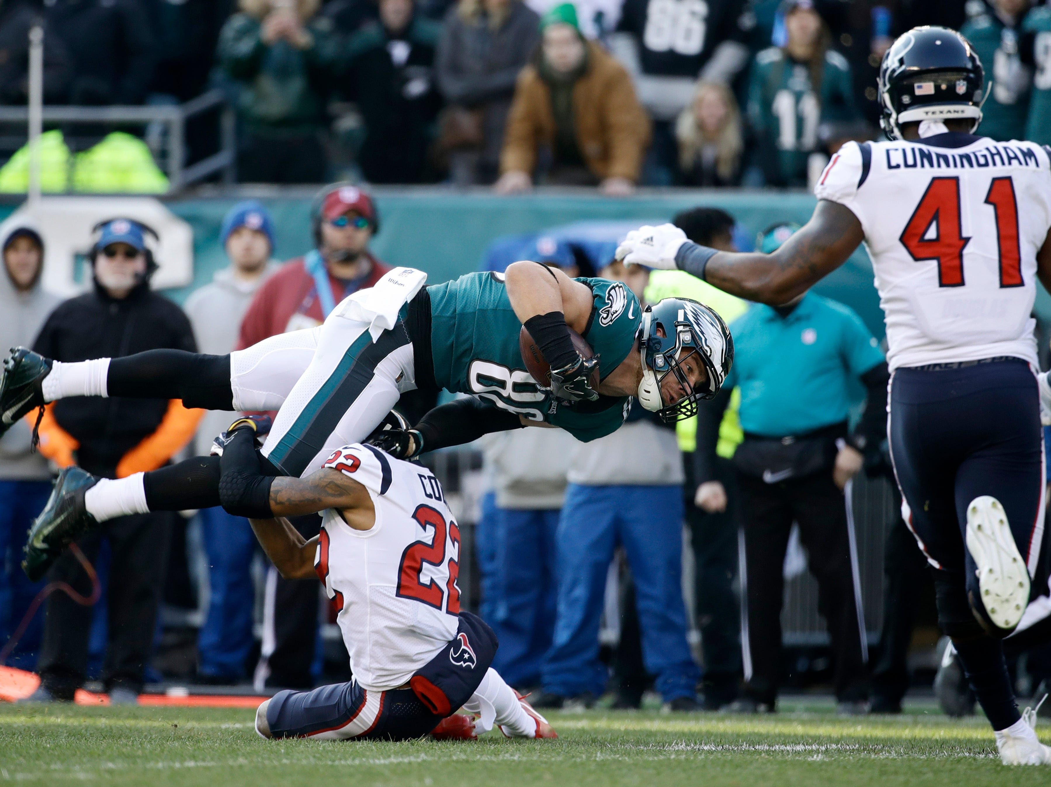 Philadelphia Eagles' Zach Ertz (86) is tackled by Houston Texans' Aaron Colvin (22) as Zach Cunningham (41) runs in during the first half of an NFL football game, Sunday, Dec. 23, 2018, in Philadelphia. (AP Photo/Matt Rourke)