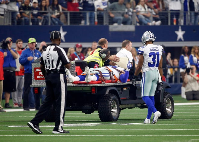 Umpire Roy Ellison (81) and Dallas Cowboys' Byron Jones (31) watch as defensive end Tyrone Crawford (98) gives a thumbs up as he is carted off the field after suffering an unknown injury in the first half of an NFL football game against the Tampa Bay Buccaneers in Arlington, Texas, Sunday, Dec. 23, 2018.