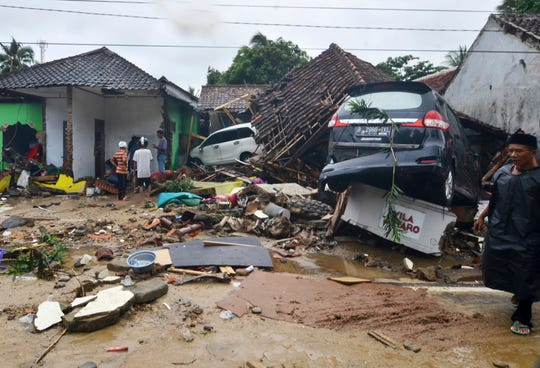 People inspect the damage at a tsunami-ravaged neighborhood in Carita, Indonesia, Sunday, Dec. 23, 2018. The tsunami occurred after the eruption of a volcano around Indonesia's Sunda Strait during a busy holiday weekend, sending water crashing ashore and sweeping away hotels, hundreds of houses and people.