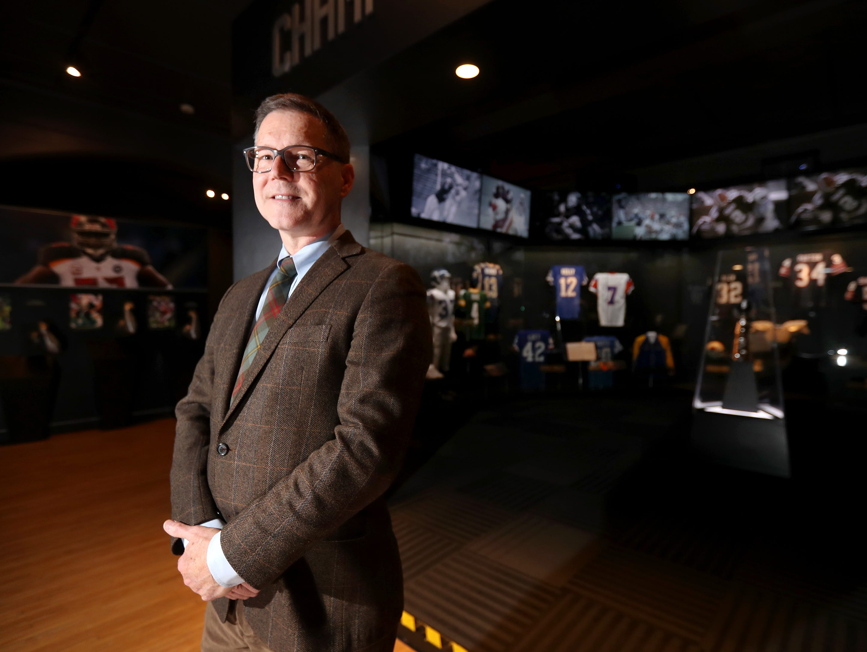 """Mat Carpenter, executive director for the History Museum at the Castle, stands for a portrait in front of the """"Gridiron Glory: The Best of the Pro Football Hall of Fame"""" exhibit Tuesday, Dec. 12, 2018, in Appleton, Wis.Danny Damiani/USA TODAY NETWORK-Wisconsin"""