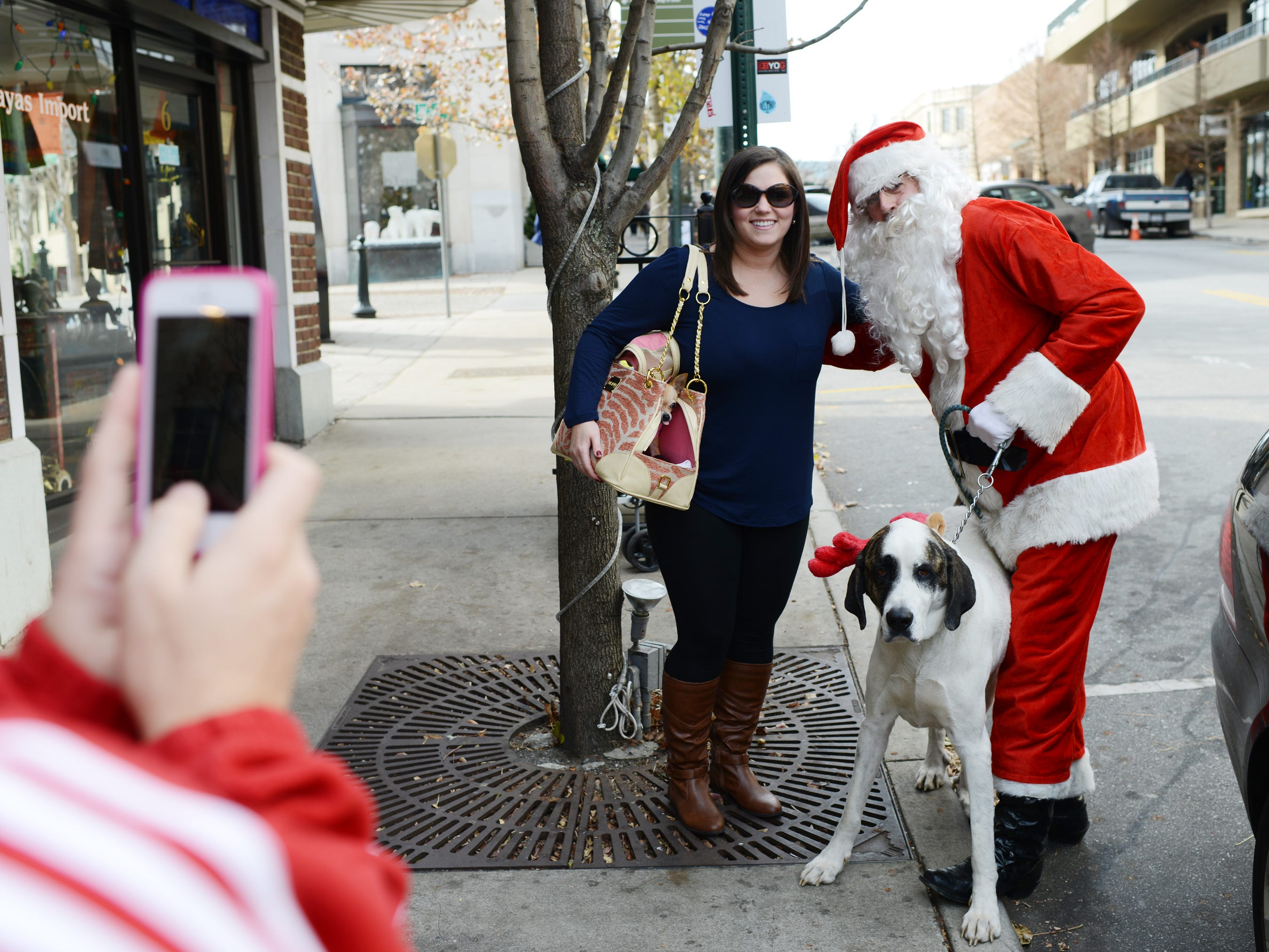 "Perry Francis makes his way through downtown dressed as Santa Claus with his dog Rowan in tow dressed as his reindeer in December 2013. Francis says he is especially happy to be spreading cheer after surviving liver cancer and getting a liver transplant last year. ""I feel blessed and have been real fortunate,"" says Francis who estimates he has been walking around ten miles a day the past week as Santa. When he and Rowan aren't walking, they're riding around town in his Studebaker Hawk."