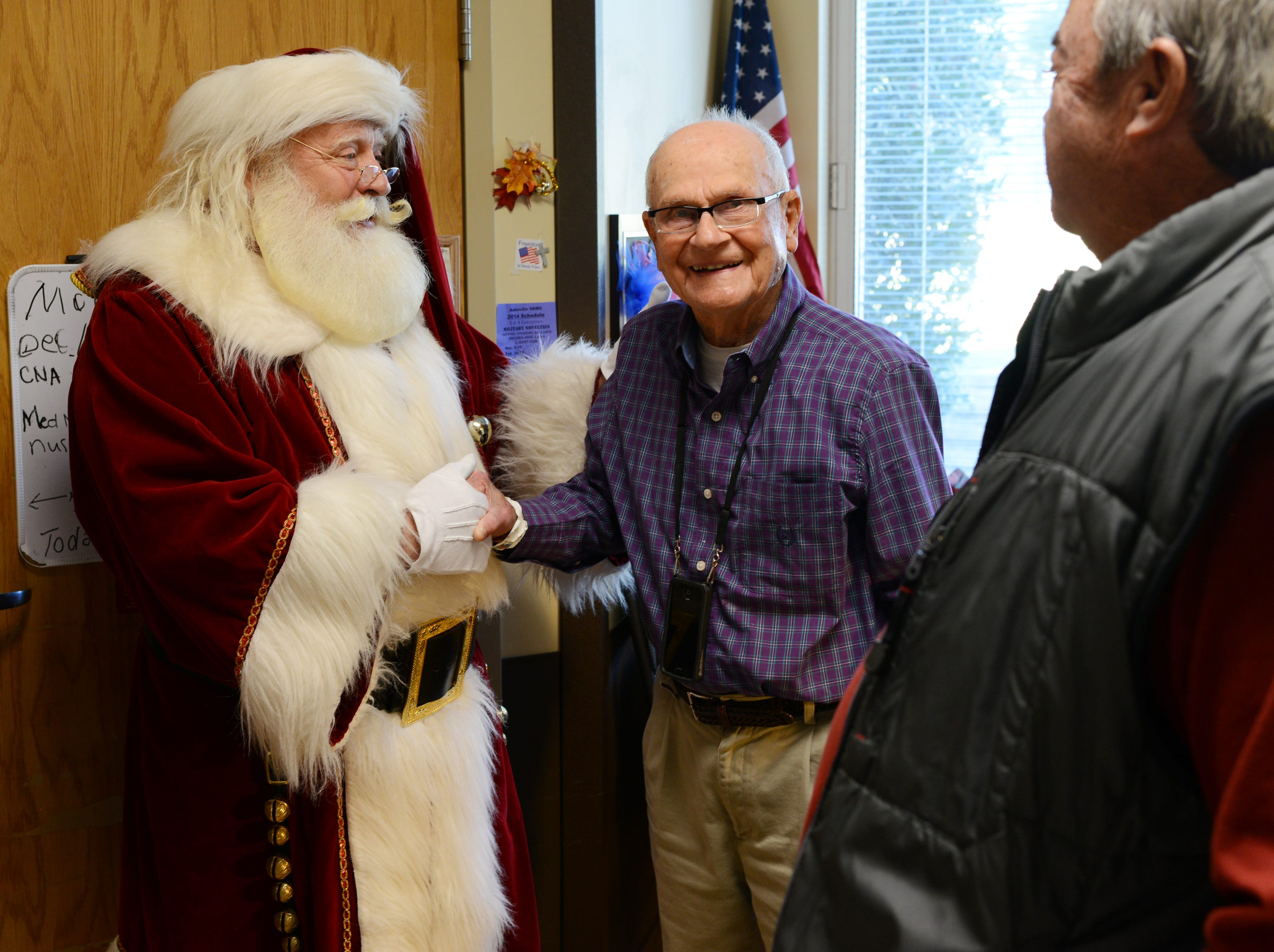 Dennis Reed, an army veteran who dresses as Santa Claus, shakes hands with Wayne Carringer, an army veteran who is staying at the VA Medical Center's community living center in December 2013. Reed and others with the Volunteers of Veterans Service Organization delivered hundreds of holiday gift bags, teddy bears and treats to veterans staying at the hospital.