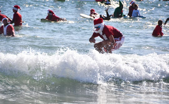 Thousands of people show up  in downtown Cocoa Beach for the annual Christmas Eve Surfing Santas event with hundreds of surfing Santas taking to the waves. The event, started by George Trosset, raises money for the Florida Surf Museum and Grind for Life.