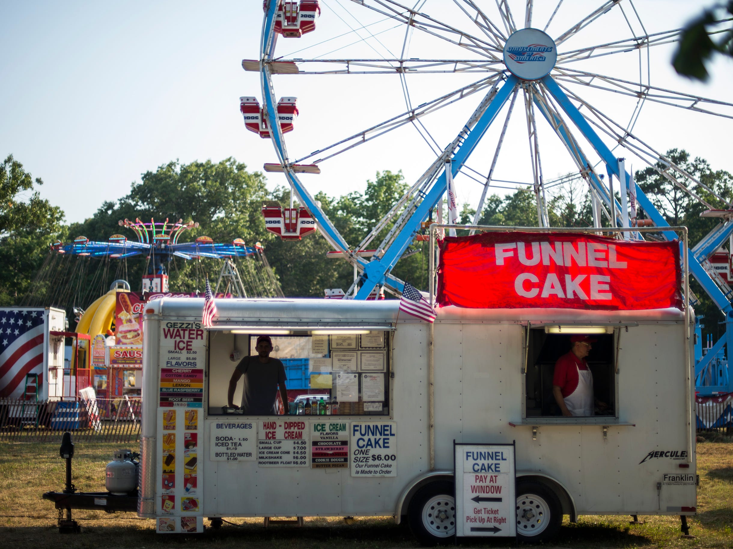 A water ice and funnel cake vendor sets up at the Cumberland County Fair Tuesday, July 3, 2018 in Millville, N.J.