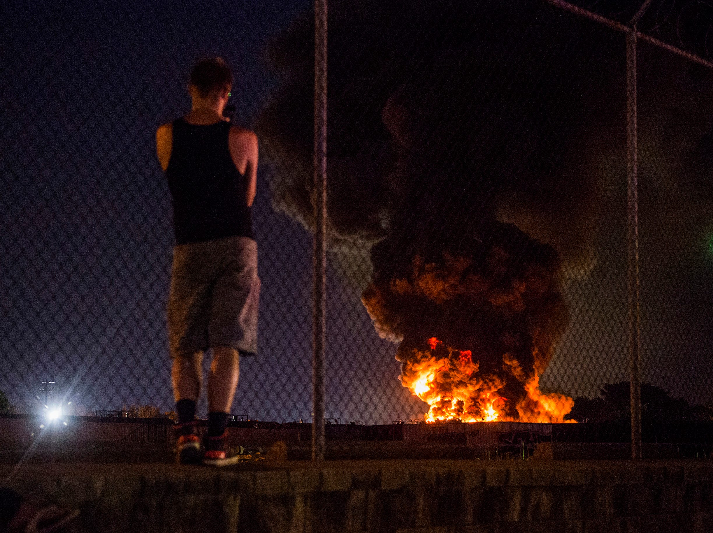 An onlooker watches as a four-alarm junkyard fire burns in the Kensington neighborhood of Philadelphia, Pa. Tuesday, July 10, 2018.