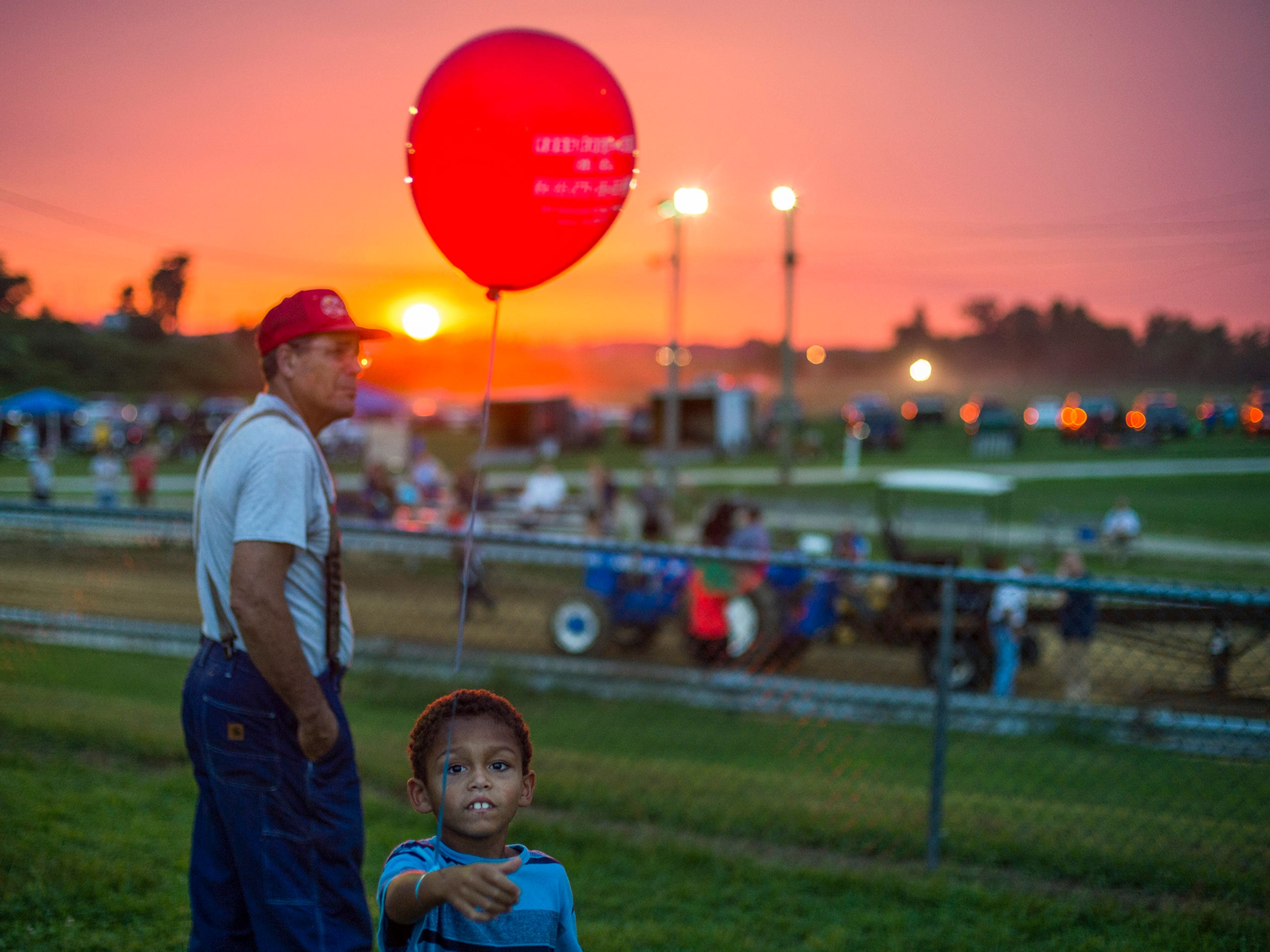A boy carries a ballon during a tractor pull competition on opening day of the Salem County Fair Tuesday, Aug. 7, 2018 in Woodstown, N.J.