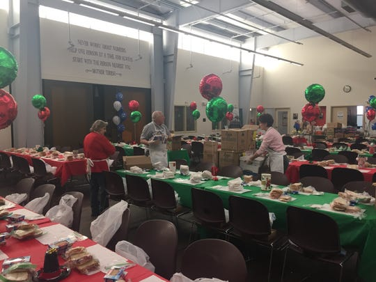 Volunteers set tables before hungry guests arrive to Cathedral Kitchen one week before Christmas.
