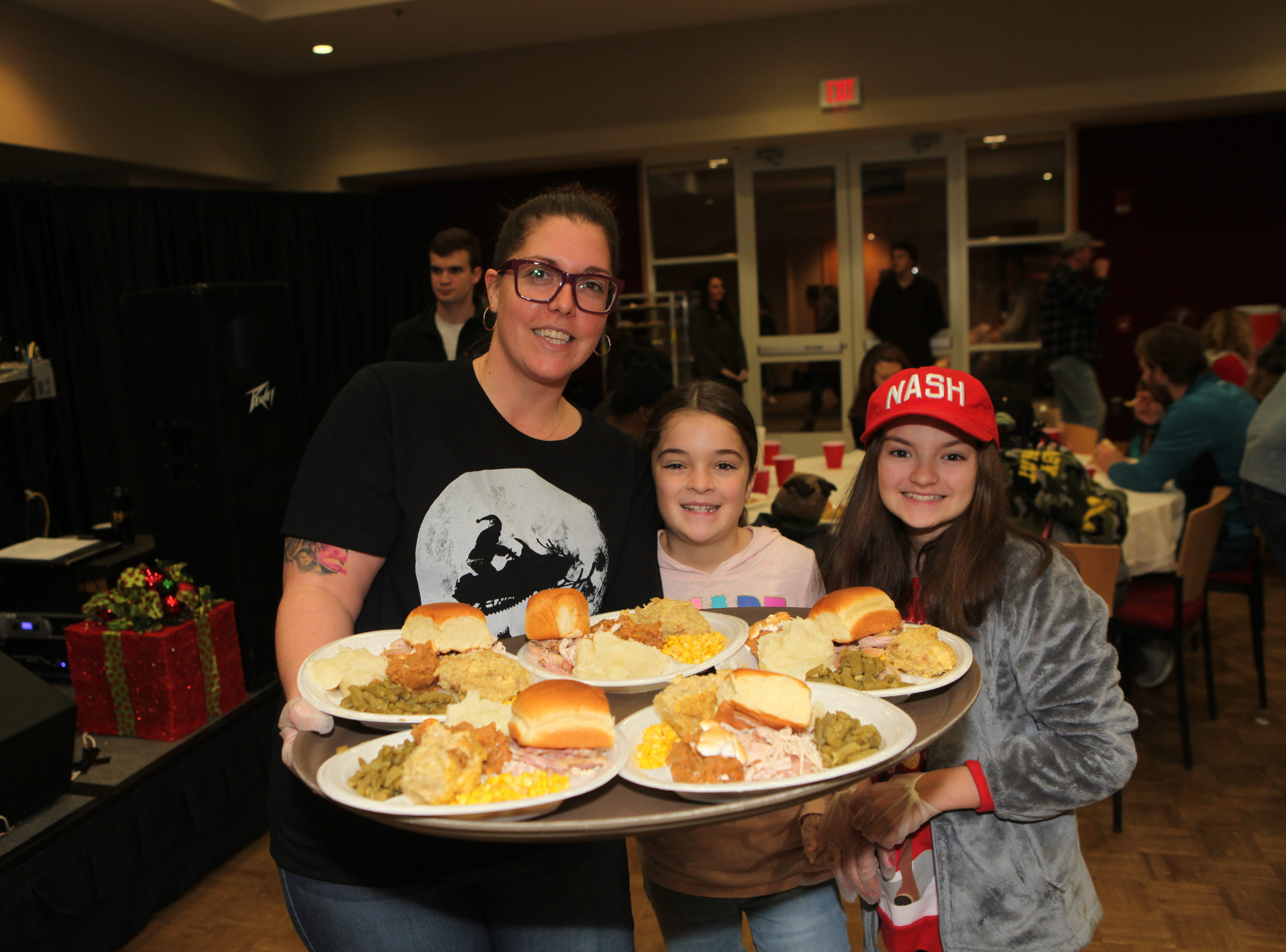 Khloe Van Hooser, Tracy Roberts and Sophia Powell deliver food during the Radical Mission's annual Warm Souls event at APSU's Morgan University Center on Christmas Eve, Dec. 24, 2018.