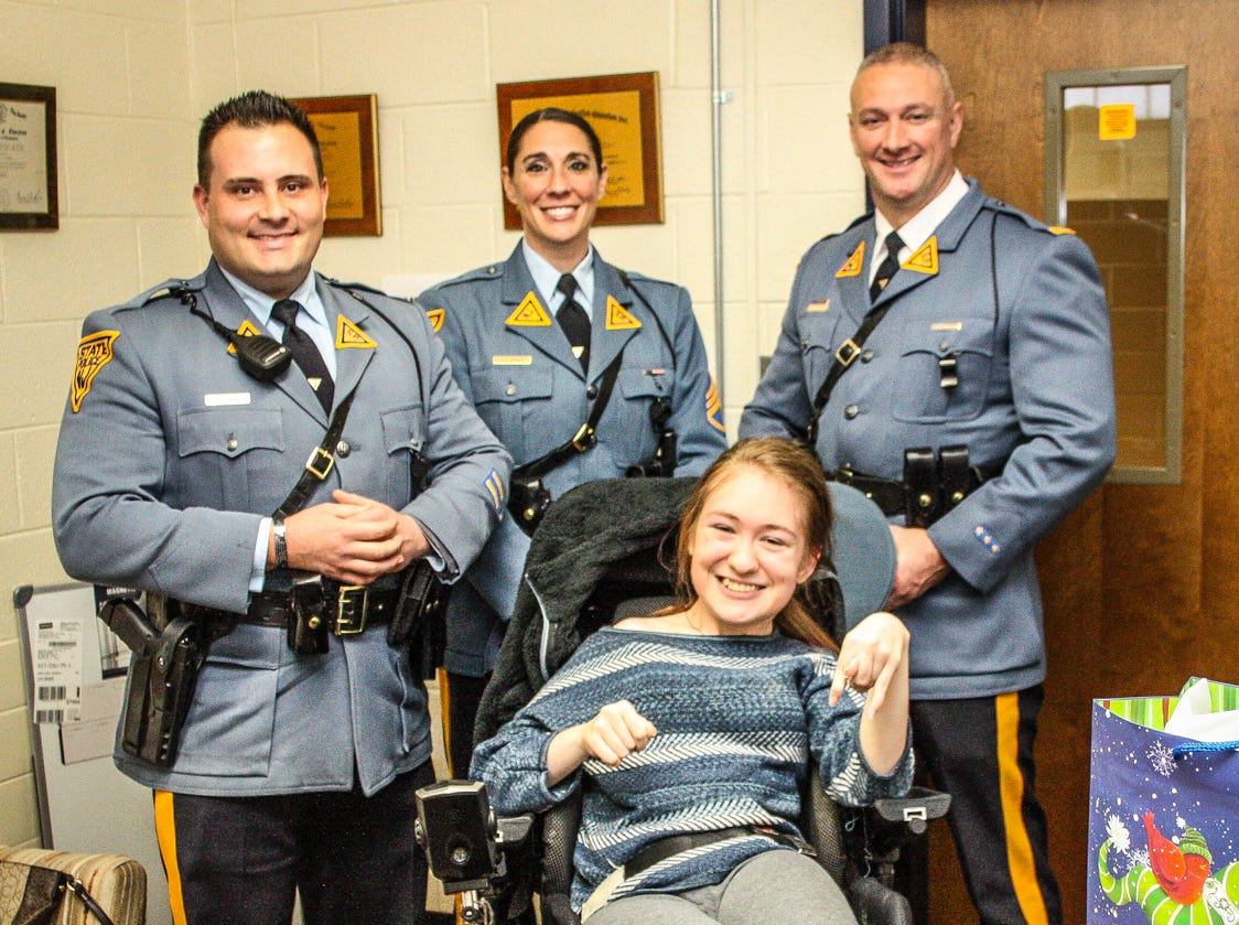 Faith Scott, a Del Val High School junior, was delighted by a shower of gifts presented to her by this delegation from the State Police stationed in Kingwood. They are, from left, Trooper Joe Seidler, Sgt. Jaclyn Juris and Lt. Sean O'Connor.
