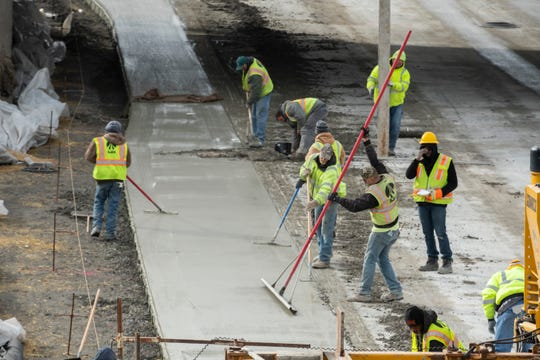 Construction workers level newly poured  concrete on I-75 near Livernois in Detroit, December 17, 2018.