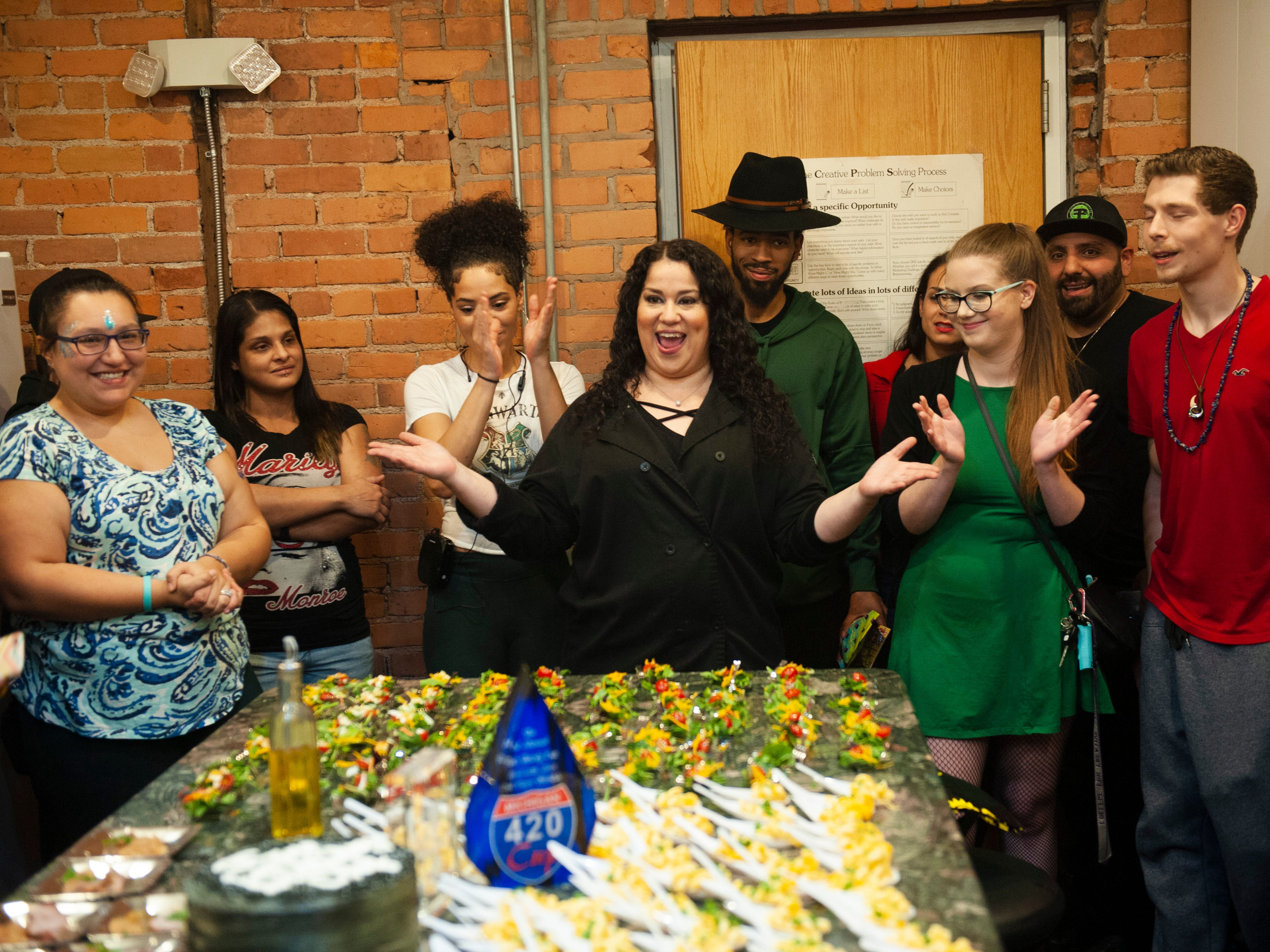 """Cannabis Concepts chef Gigi Diaz, center, celebrates her birthday by welcoming event guests to sample THC-infused edibles from sweets to pork loin, salad to mac and cheese, have a good time and """"get lit"""" during """"The Art of Cannabis"""" tasting and art exhibition at the Cannabis Counsel in Detroit on Saturday, Dec. 22, 2018. Guests bought a ticket to the event, but once inside were treated to free samples of cannabis edibles."""