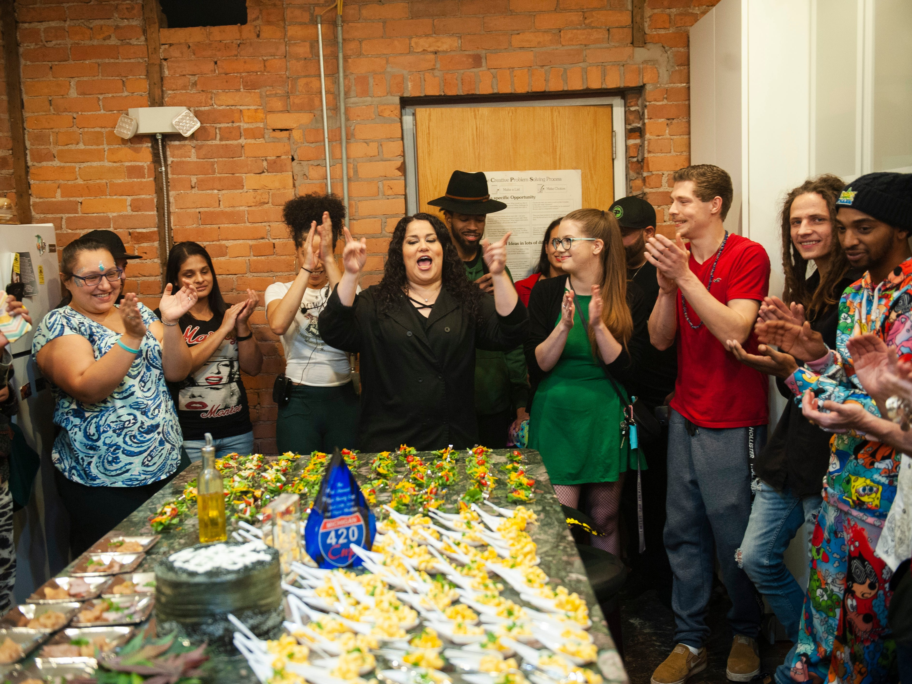 """Cannabis Concepts chef Gigi Diaz, center, celebrates her birthday by welcoming event guests to sample THC-infused edibles from sweets to pork loin, salad to mac and cheese, have a good time and """"get lit"""" during """"The Art of Cannabis"""" tasting and art exhibition at the Cannabis Counsel in Detroit on Saturday, Dec. 22, 2018."""