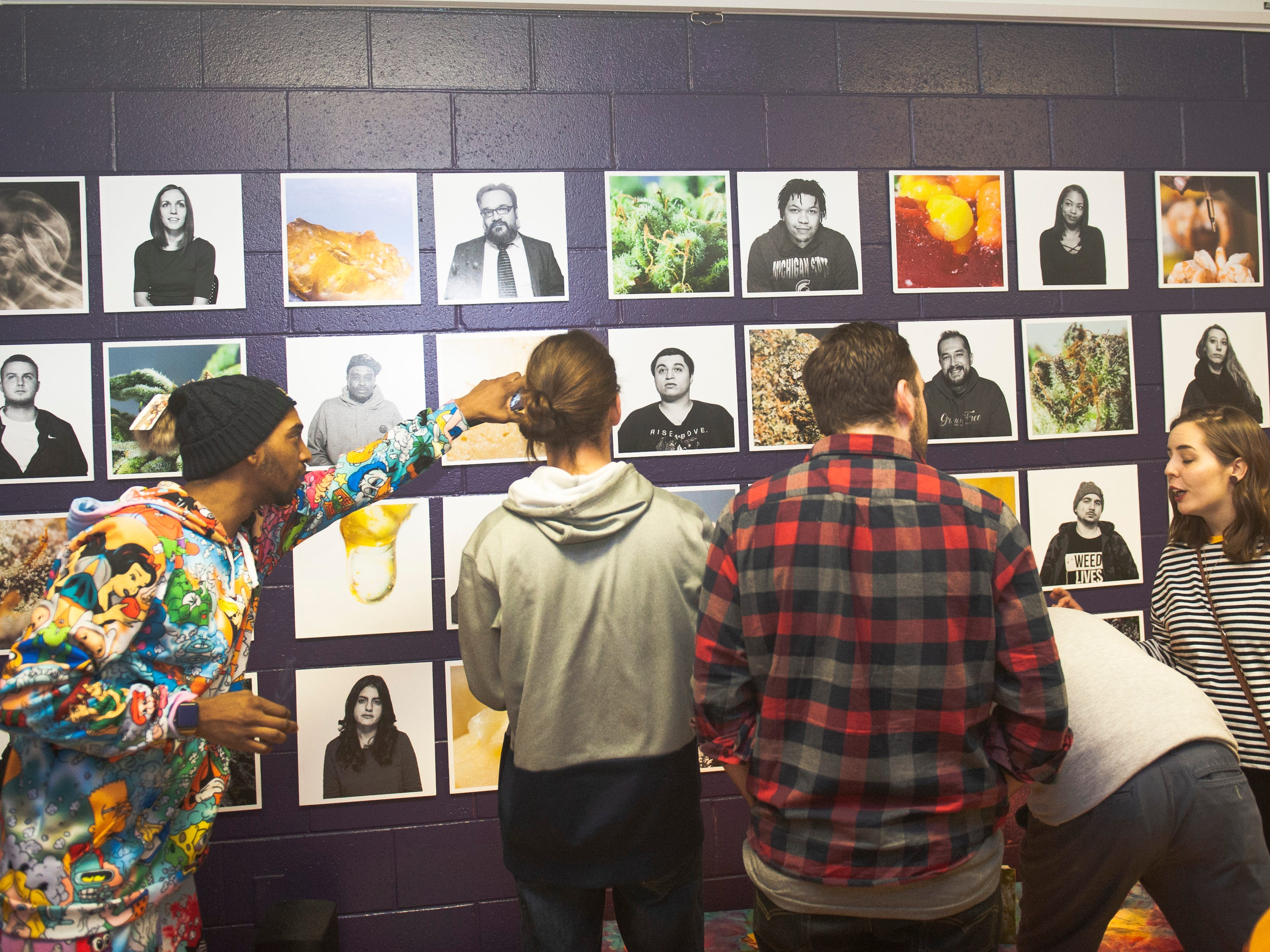 """Event guests check out the art of photographer Erin Short, the featured artist at """"The Art of Cannabis"""" exhibition and tasting event at the Cannabis Counsel in Detroit. Short's CCS senior thesis project explored the lives of Michigan medical marijuana patients and their preferred methods of using cannabis."""