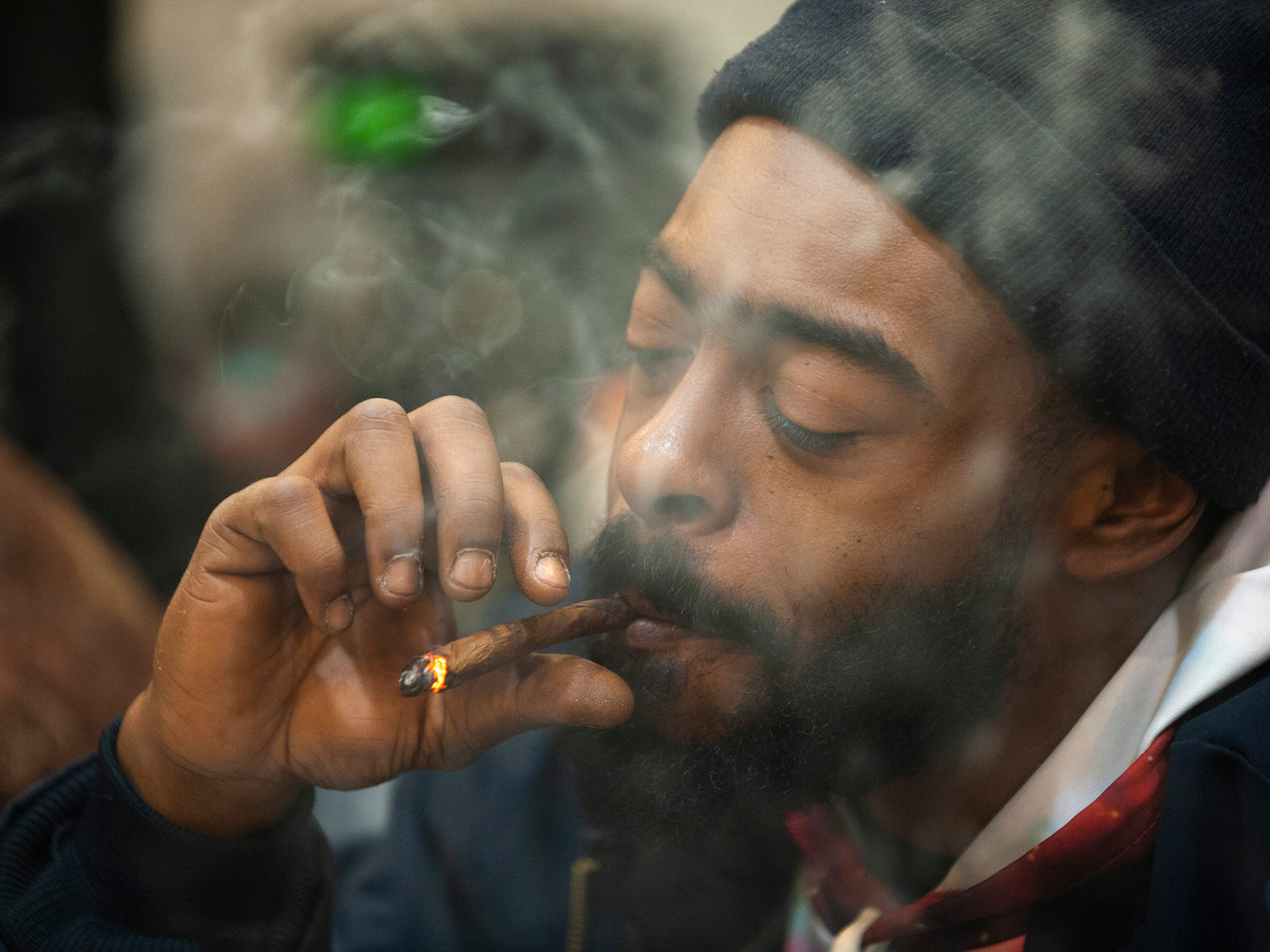 """Corey Faison of Inkster puffs on a blunt, marijuana rolled up in a cigar wrap, during """"The Art of Cannabis"""" event at the Cannabis Counsel in Detroit."""