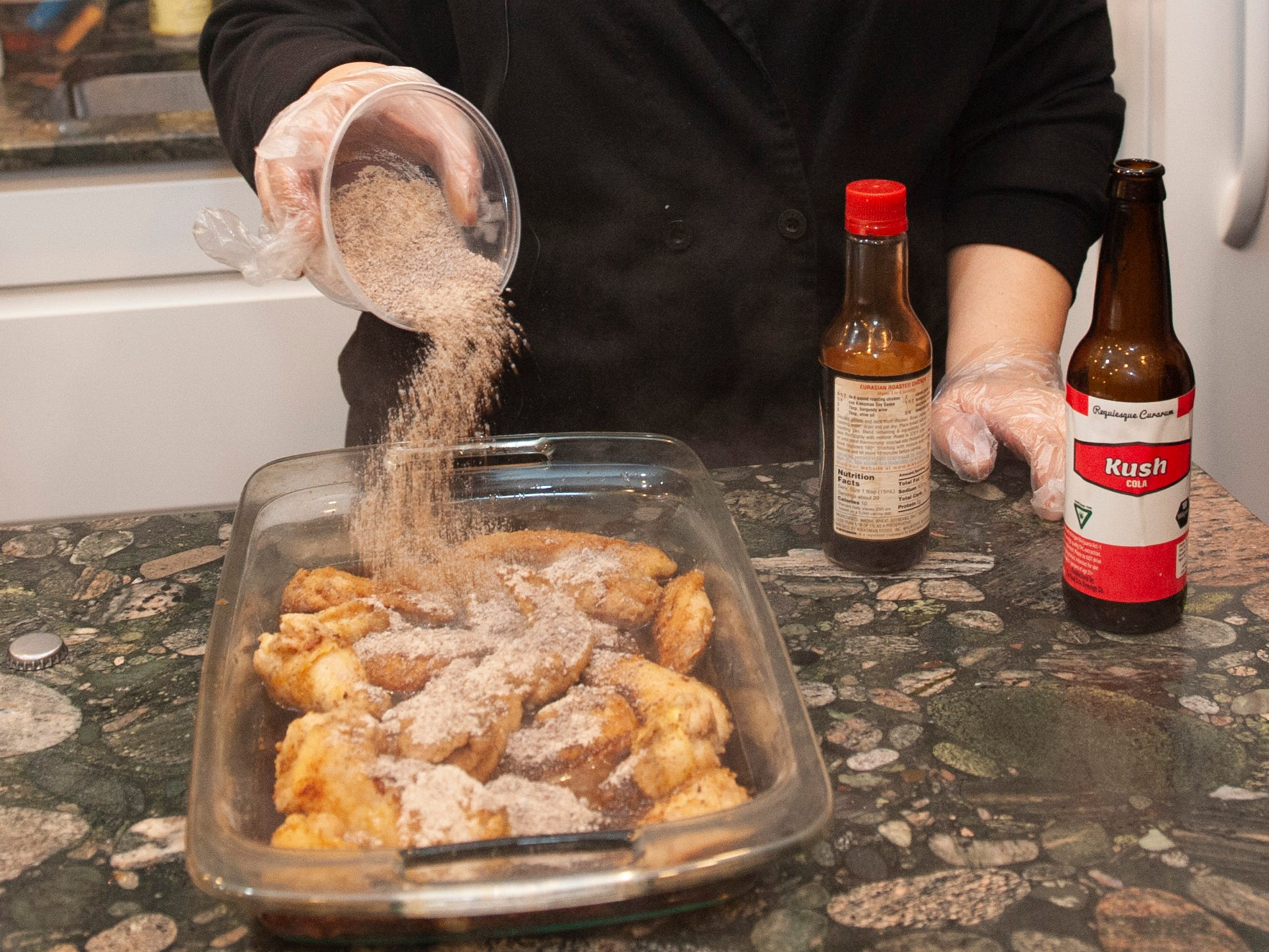 """Cannabis Concepts chef Gigi Diaz, who won High Times magazine's 2017 chef of the year award, pours cannabis-infused brown sugar over her recipe for sweet cola chicken wings during a cooking demonstration at """"The Art of Cannabis"""" tasting and art exhibition at the Cannabis Counsel in Detroit on Dec. 22, 2018."""