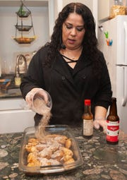 "Cannabis Concepts chef Gigi Diaz, who won High Times magazine's 2017 chef of the year award, pours cannabis-infused brown sugar over her recipe for sweet cola chicken wings during a cooking demonstration at ""The Art of Cannabis"" tasting and art exhibition at the Cannabis Counsel in Detroit on Dec. 22, 2018."
