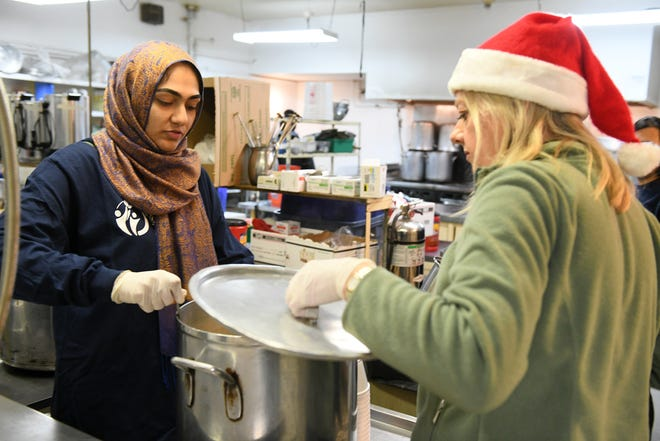 Mercy-USA for Aid and Development volunteer Hibah Naseer  22 of Canton, left, checks on a pot of soup with volunteer from Northville, Karen Schaumann. Muslim volunteers organized by Mercy-USA for Aid and Development serve food at St. Peter's Episcopal Church in Detroit on Dec. 24, 2018.