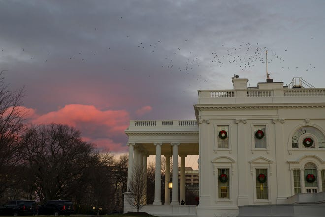 The setting sun illuminates clouds behind the White House during a partial federal shutdown, Saturday, Dec. 22, 2018, in Washington.