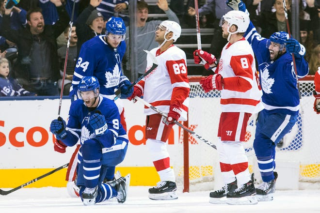 Toronto's John Tavares, left, celebrates after scoring the tying goal in the final seconds of third period on Sunday. The Leafs would go on to hand the Red Wings their sixth loss in seven games with a 5-4 overtime win.