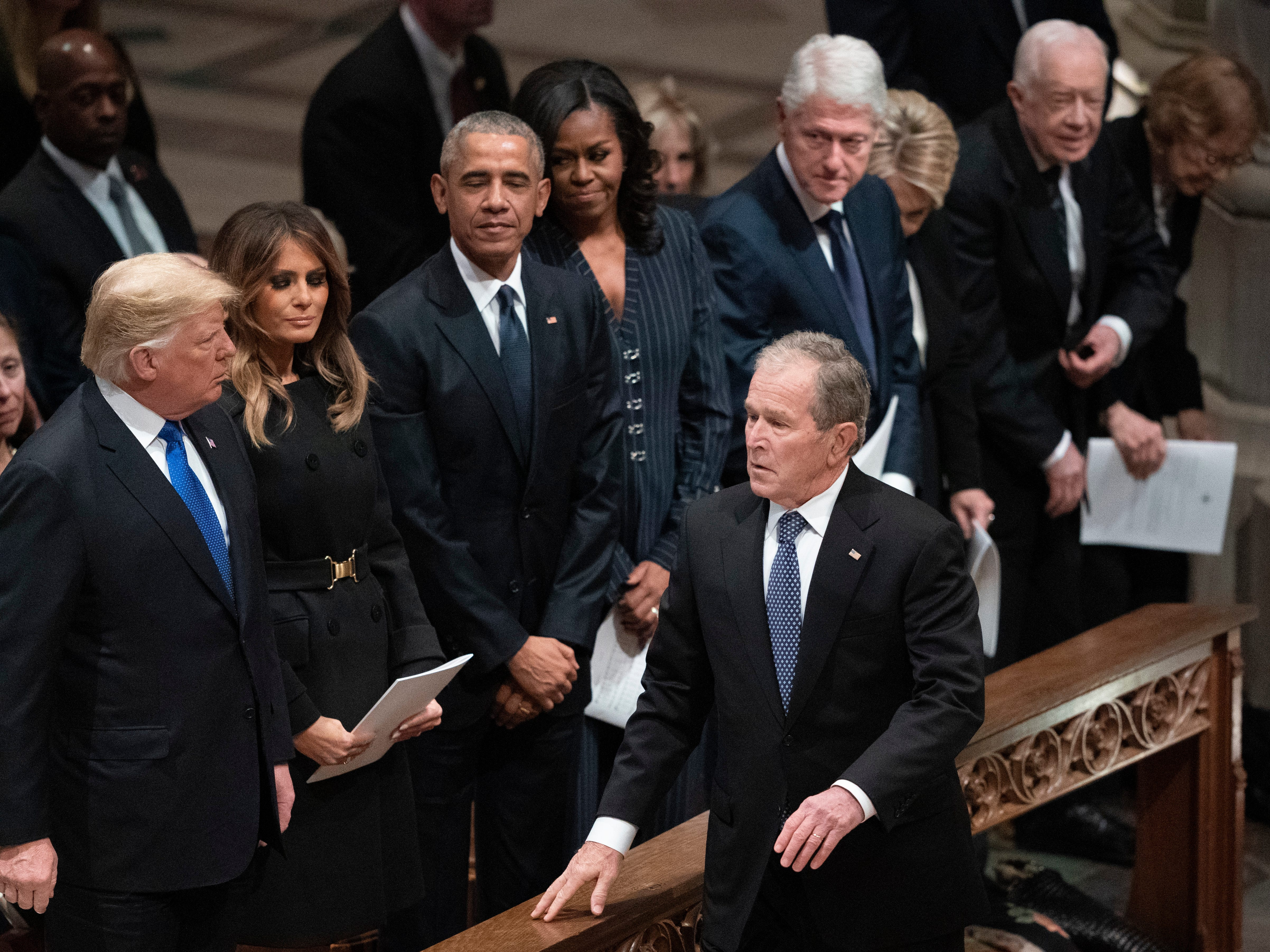 President George W. Bush walks to his seat after greeting President Donald Trump, first lady Melania Trump, former President Barack Obama, Michelle Obama, former President Bill Clinton, former Secretary of State Hillary Clinton, former President Jimmy Carter, and Rosalynn Carter during a State Funeral for former President George H.W. Bush at the National Cathedral,  Dec. 5, 2018, in Washington.