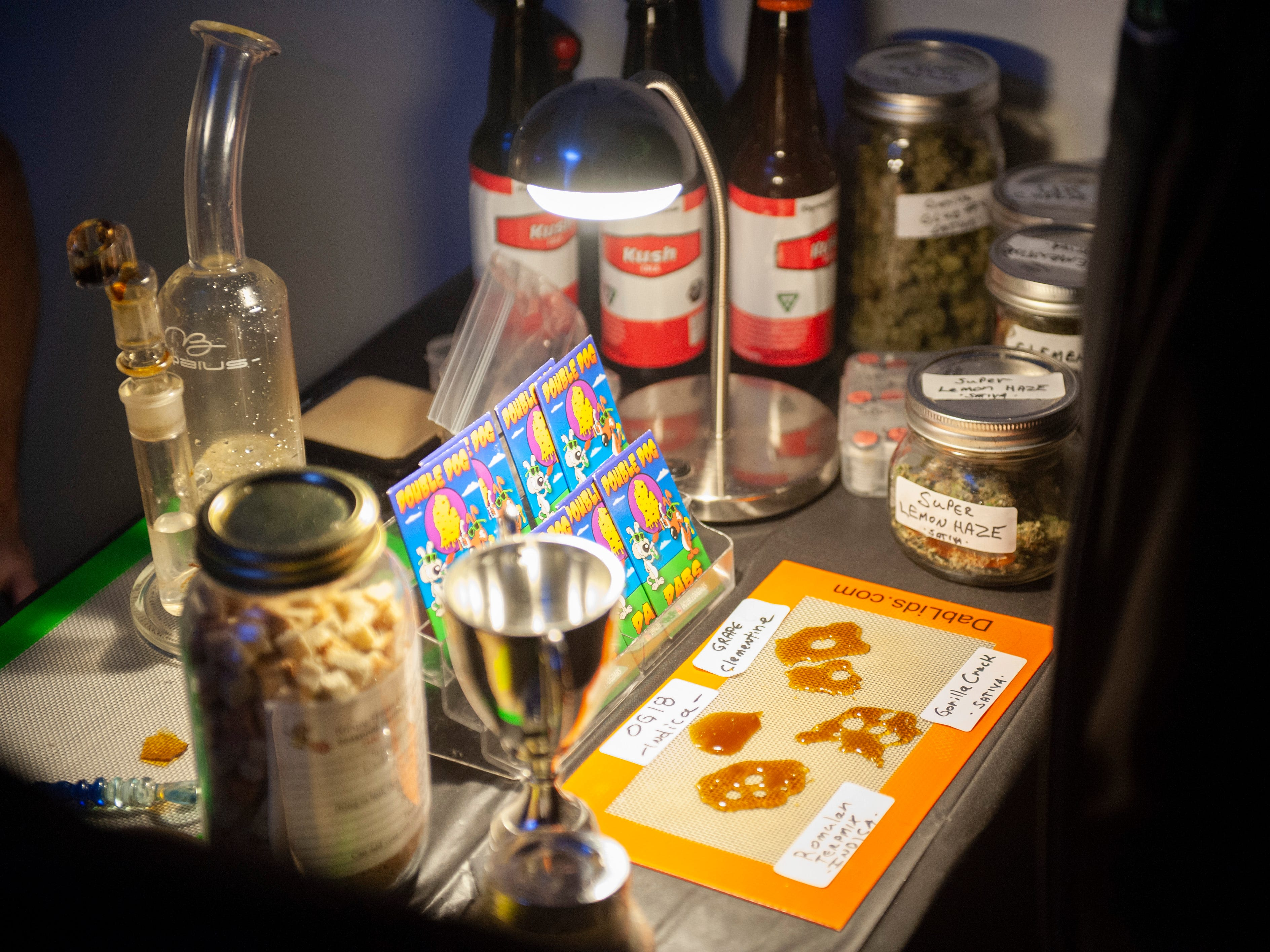 """Double Dog Dabs display of cannabis products including """"dabs,"""" which are condensed THC resins usually smoked in a glass bong and various strains of marijuana buds and THC-infused Kush Cola at """"The Art of Cannabis"""" event."""