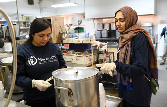 Mercy-USA for Aid and Development volunteers Hibah Naseer, 22 of Canton Township, right, and Hinah Qadir 31, of Warren talk before switching places in the food serving line.