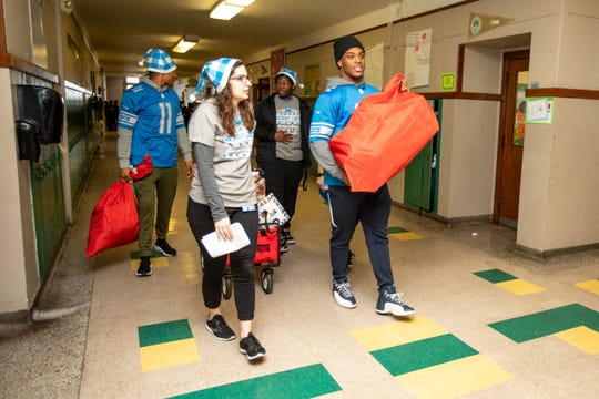 Detroit Lions wide receiver Marvin Jones Jr. (11) and Detroit Lions linebacker Devon Kennard (42) deliver holiday gifts to students at Mary McLeod Bethune Elementary-Middle School last week.