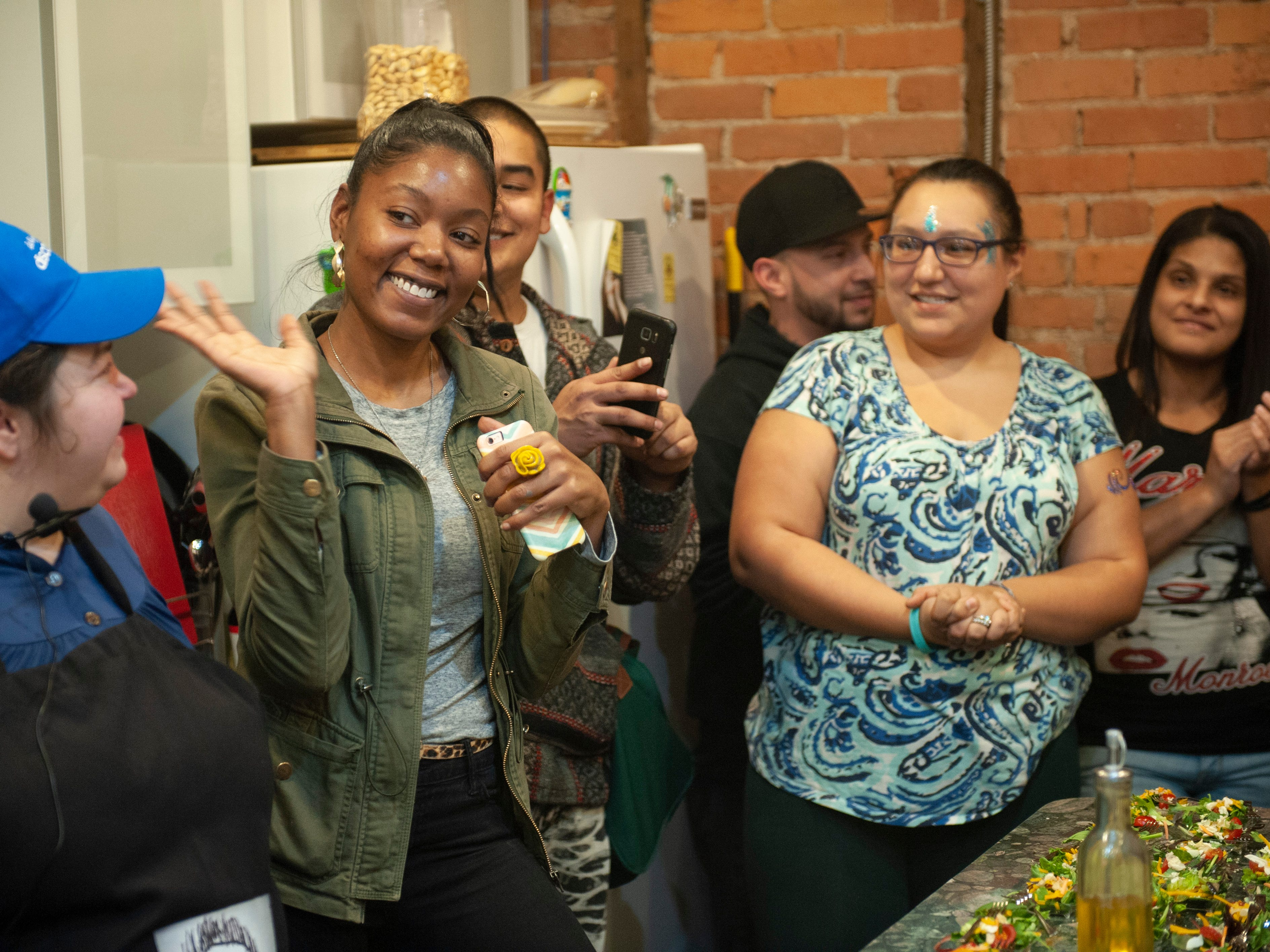 """Cannabis entrepreneur Adrienne Benson of AB Blooms in Ypsilanti waves to party guests as she is introduced at the beginning of """"The Art of Cannabis"""" tasting and art exhibition."""