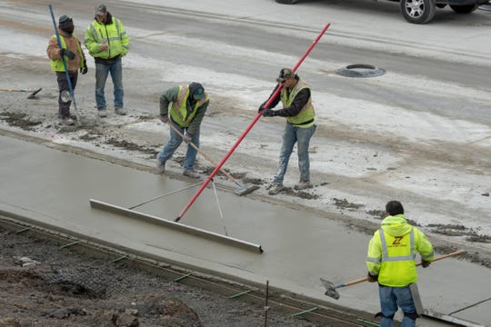 With temperatures in the low 30s, construction workers level concrete on I-75 near Livernois in Detroit on December 17, 2018.  Heaters are used to keep fresh concrete from freezing and cracking in cold temperatures.
