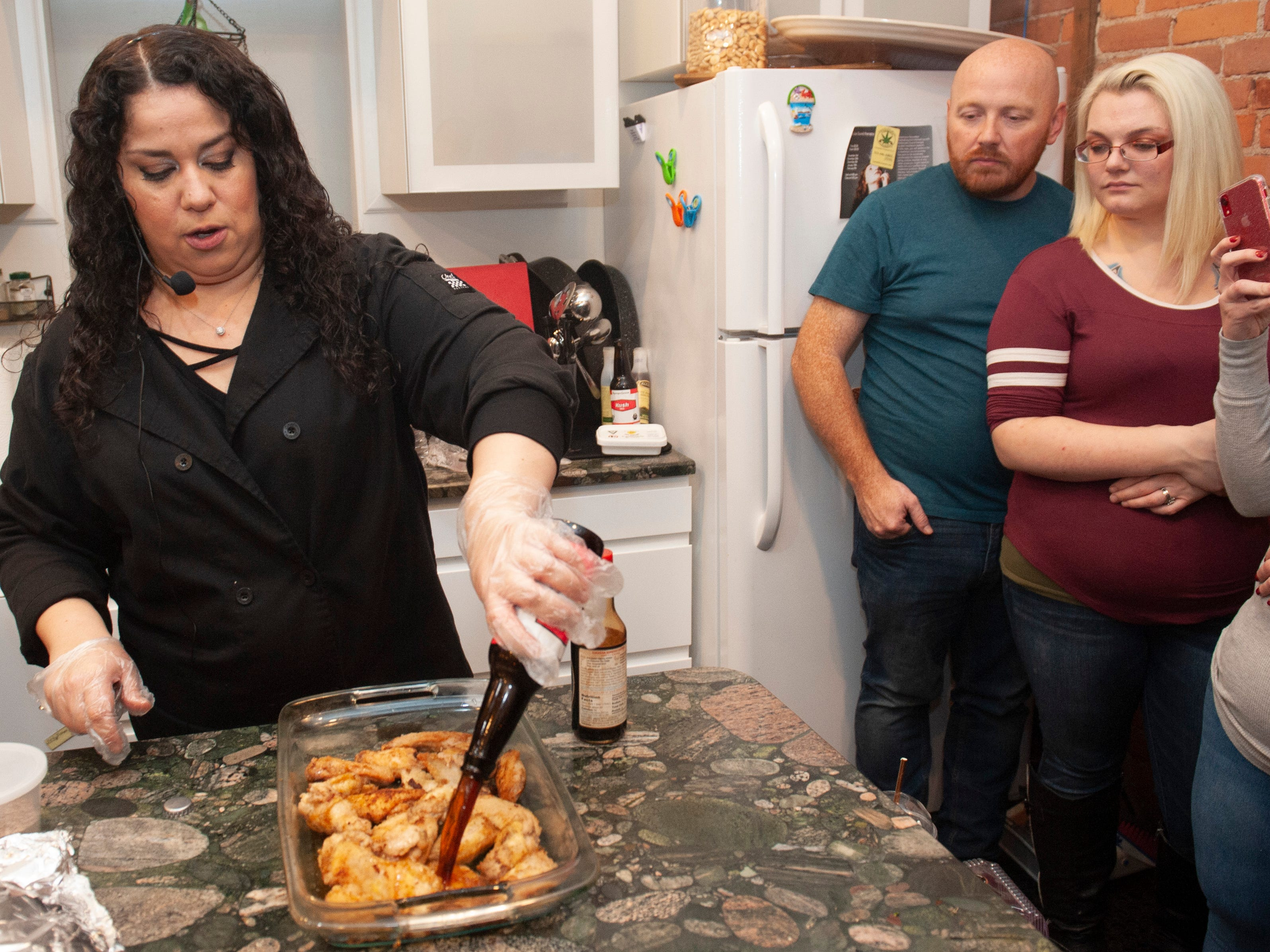 """Cannabis Concepts chef Gigi Diaz, who won High Times magazine's 2017 chef of the year award, pours THC-infused Kush Cola over her recipe for sweet cola chicken wings during a cooking demonstration at """"The Art of Cannabis"""" tasting and art exhibition at the Cannabis Counsel in Detroit on Dec. 22, 2018."""