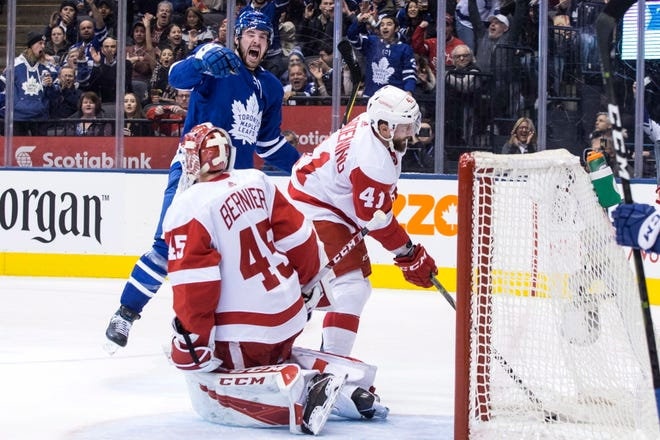 Detroit Red Wings' Luke Glendening (41) retrieves the puck from the net as Toronto Maple Leafs' Frederik Gauthier celebrates after scoring his team's second goal against Red Wings goaltender Jonathan Bernier during second period.