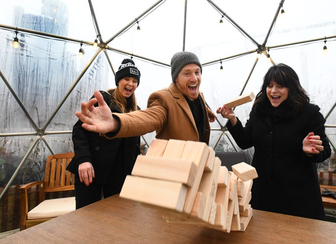 Alec Penix, center, topples Jenga blocks with his girlfriend, Jessica Filoramo, and mother, Linda Searles, in a dome in downtown Detroit last week.