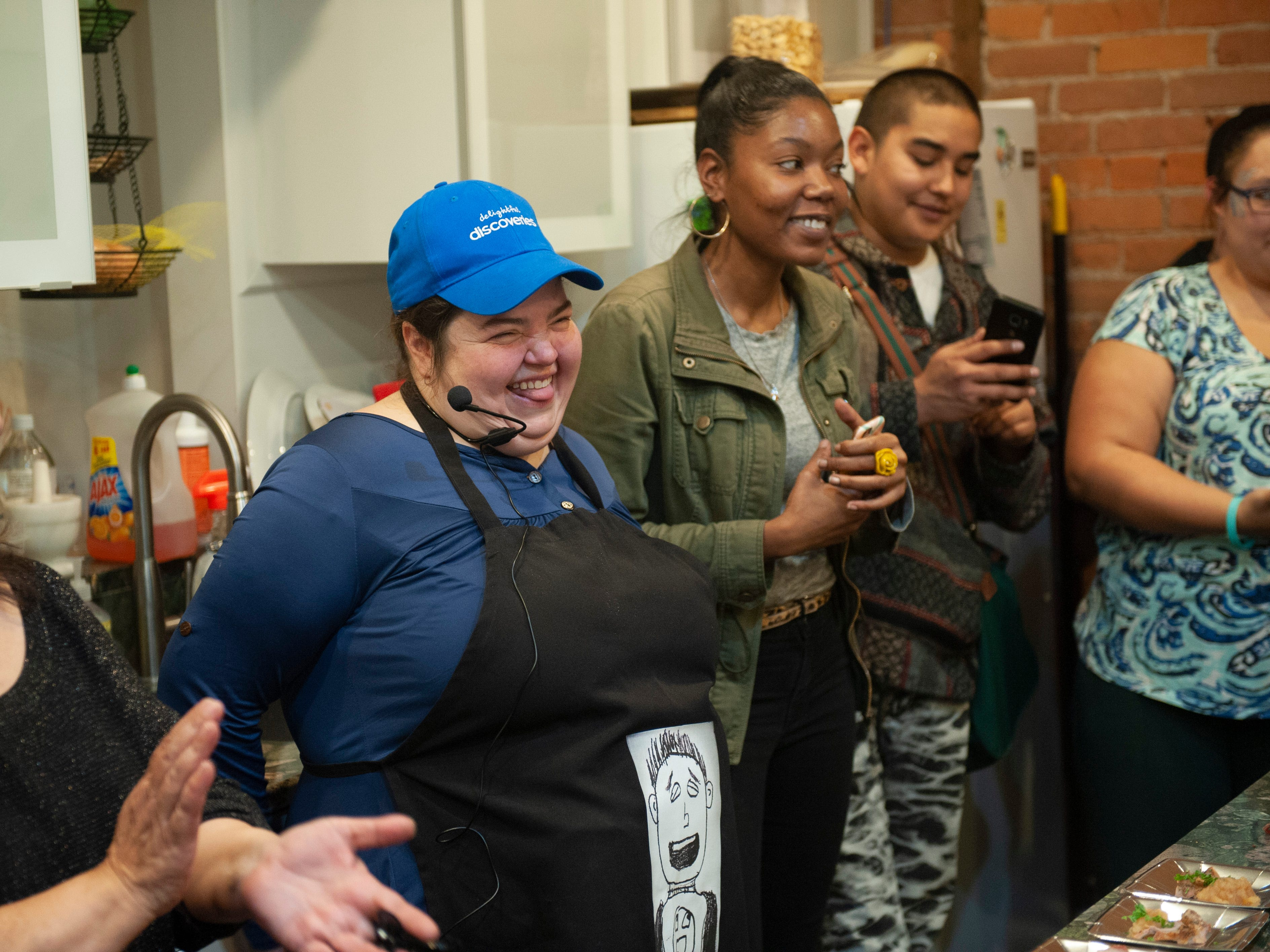 """Cannabis chef Karla Galli, center, of Krispy Treats Kitchen smiles as she is introduced to the party guests at the beginning of """"The Art of Cannabis"""" tasting and art exhibition at the Cannabis Counsel in Detroit."""