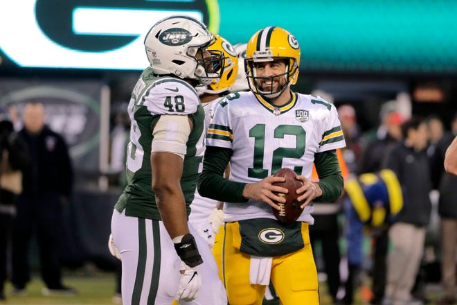 Green Bay Packers quarterback Aaron Rodgers (12) talks to New York Jets outside linebacker Jordan Jenkins (48) during the second half on Sunday.