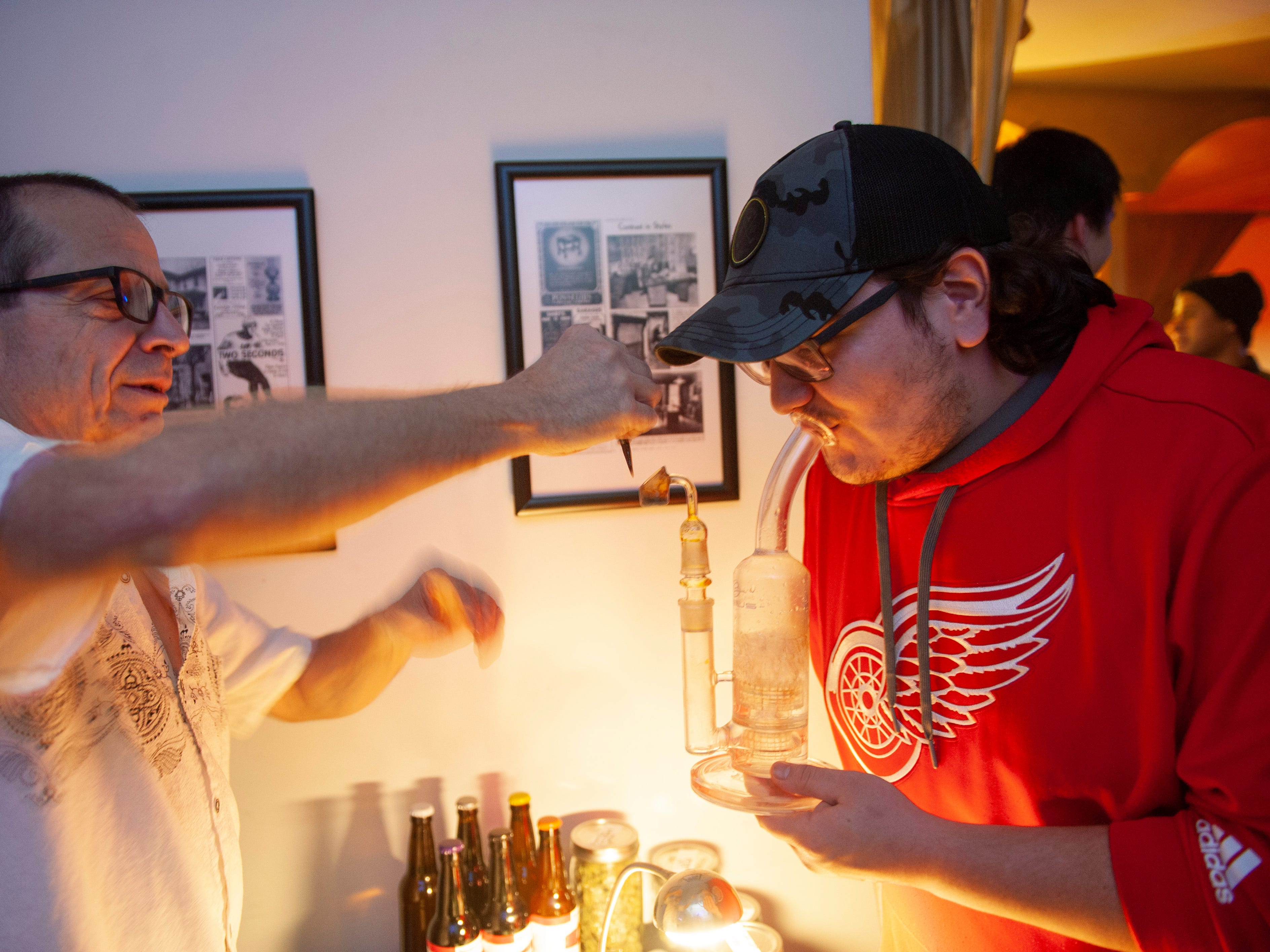 """Cannabis entrepreneur Mike, left, offers a free """"dab"""" to Peter of Oakland Township (both withheld their last names) during """"The Art of Cannabis"""" event at the Cannabis Counsel in Detroit."""