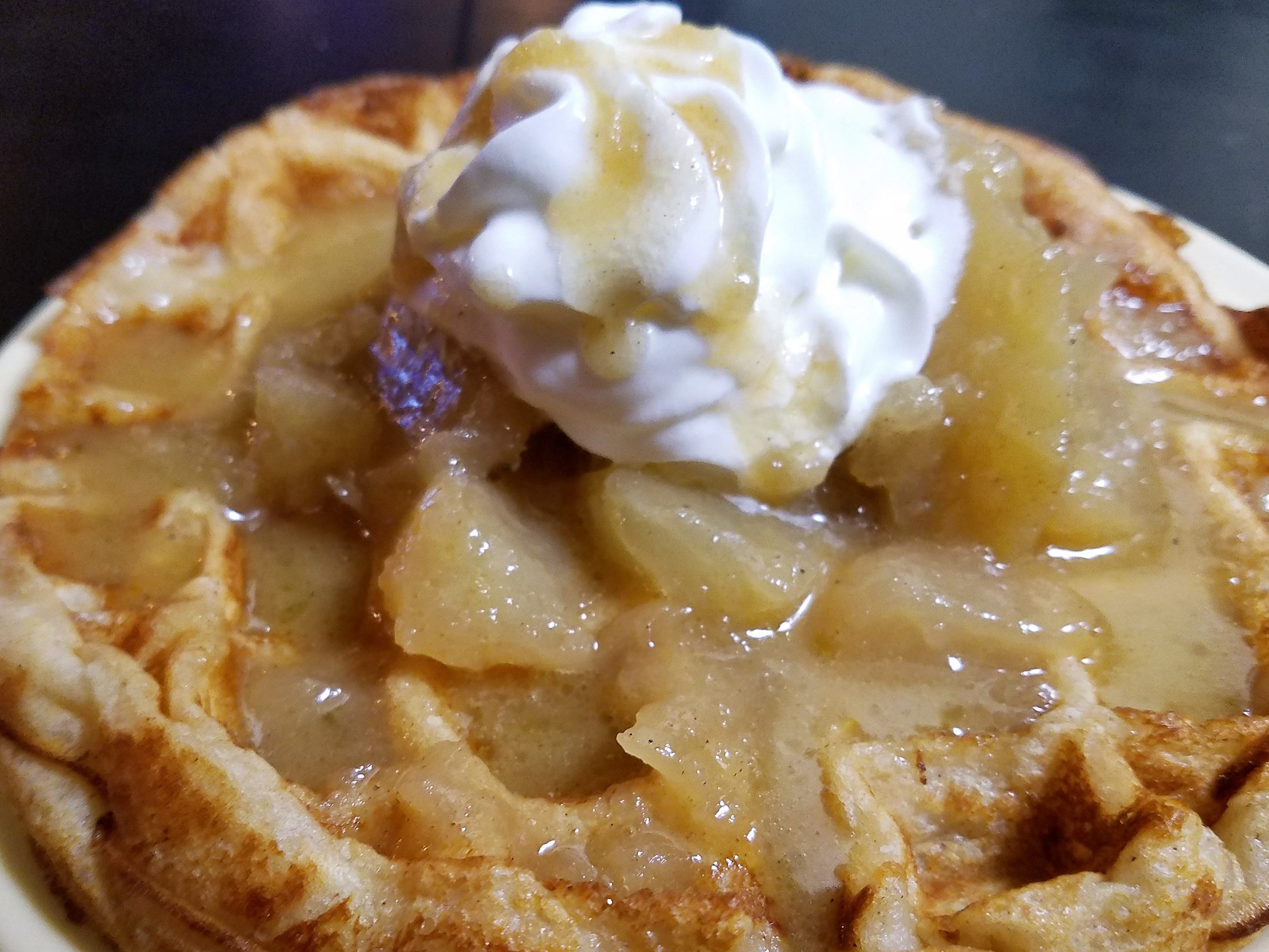 A freshly-made waffle topped with fried apples and whipped cream at Piston's Bar and Grill.