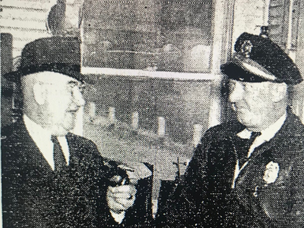 Former Henderson mayor and toll booth supervisor L.L. Hurley speaks with a police officer in 1941.